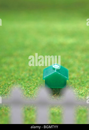 Monopoly house on green grass with white picket fence. - Stock Photo