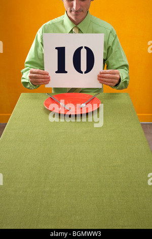 man eating at table holds up 10 sign to rate dinner - Stock Photo
