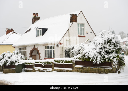 Detached house and shrubs covered in winter snow at Newport South Wales UK - Stock Photo
