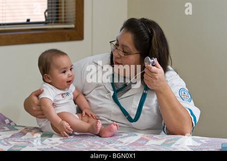 Nurse examines baby in health care office