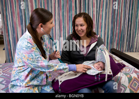 Native American nurse examines an infant at a medical center
