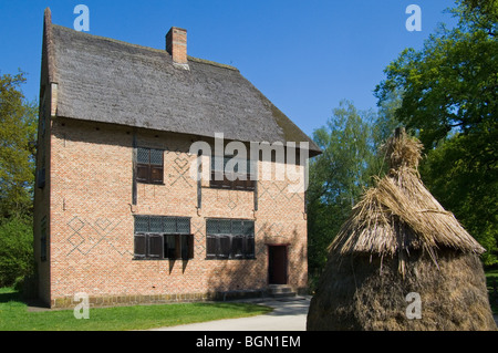 Haystack and traditional brick house in the open air museum Bokrijk, Belgium - Stock Photo