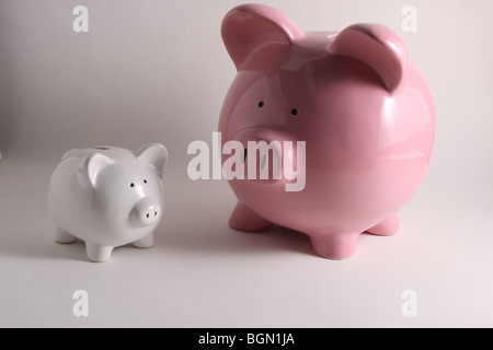 two piggy banks. One large pink piggy bank and one small white piggy bank - Stock Photo
