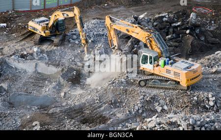 Crawler excavators on a building demolition yard - Stock Photo