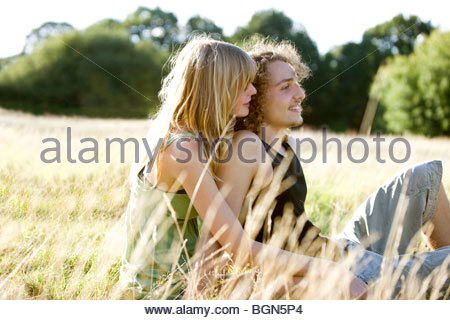 A romantic young couple sitting on the grass in summertime - Stock Photo