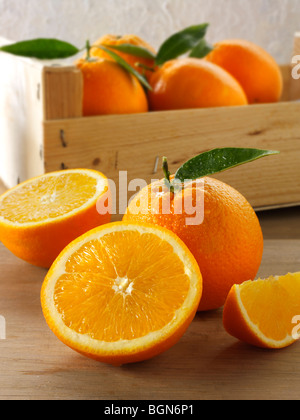 Fresh oranges whole and cut halves with leaves in a box - Stock Photo