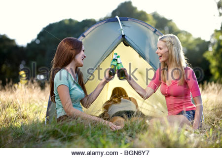Three young women camping, two drinking beers - Stock Photo