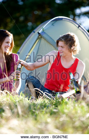 A young couple sitting in front of a tent, drinking beer - Stock Photo