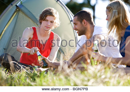 Three young people sitting in front of a tent, drinking beer - Stock Photo