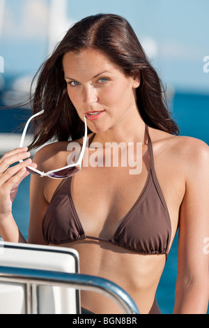 Young woman sailing on luxury yacht sunbathing in bikini - Stock Photo