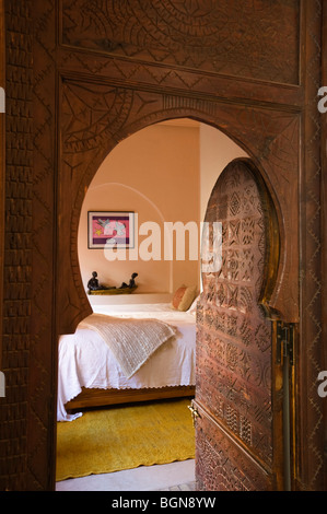 Carved doorway opens to bedroom of a riad in the Medina of Marrakesh - Stock Photo