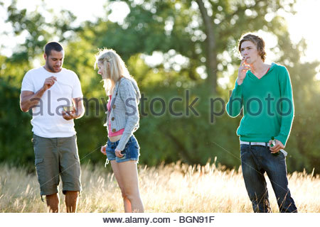 Three young friends standing in a field, eating, drinking and smoking - Stock Photo