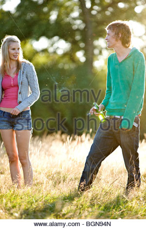 A young couple standing in a field, man drinking and smoking - Stock Photo