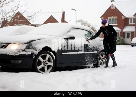 A woman clearing snow from her car on her driveway in Worcestershire, UK - Stock Photo