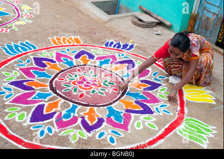Indian woman making a Rangoli festival design in an Indian street at the hindu festival of Sankranthi. Puttaparthi, - Stock Photo