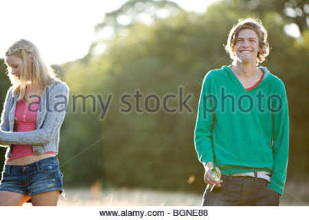 Two young friends standing in a field, one smoking - Stock Photo