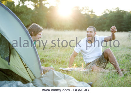 Two young men sitting next to a tent, having a barbecue - Stock Photo