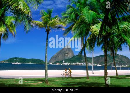People biking along Flamengo Beach near Sugar Loaf Mountain in Rio de Janeiro Brazil - Stock Photo