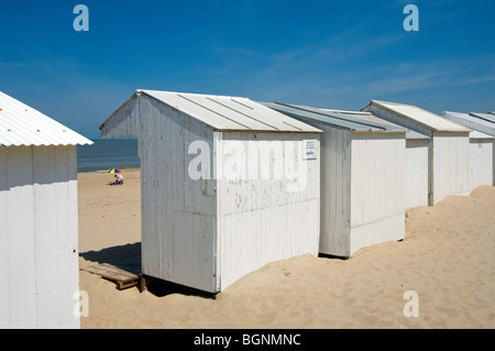 Row of white beach cabins along the North Sea coast at seaside resort Koksijde / Coxyde, West Flanders, Belgium - Stock Photo