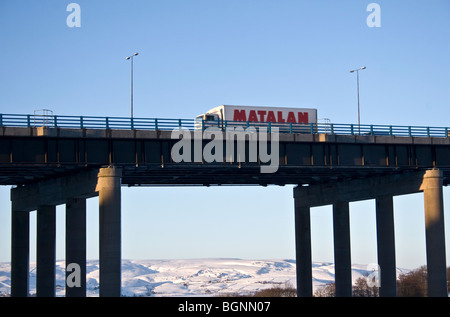 Truck coming down from Pennines on  M62 motorway viaduct near Rochdale,  UK. Hollingworth Lake, Littleborough beyond. - Stock Photo