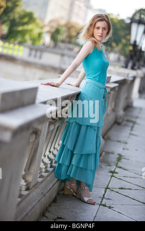 Young slim woman in dress standing at the railing. - Stock Photo