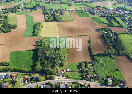 Urbanisation at the border of agricultural area with fields, grasslands and hedges from the air, Belgium - Stock Photo