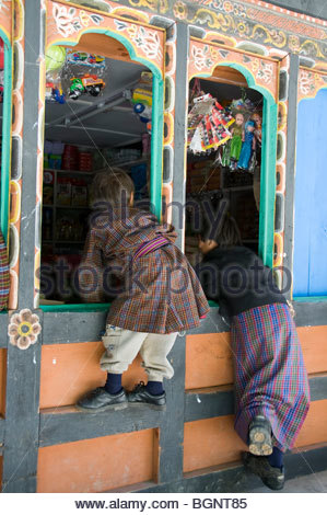 Boy and Girl Looking Through A Shop Window At The Television Set Inside In Bumthang, Bhutan on the Day of the Coronation - Stock Photo