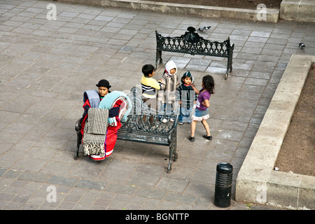 impassive indigenous Indian woman draped in textiles for sale sits on Zocalo iron bench while scruffy children play - Stock Photo