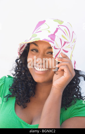 Portrait of a young woman wearing a hat and smiling - Stock Photo