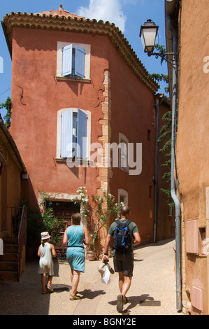 Tourists walking in the streets of Roussillon with its ochre coloured houses, Provence, Provence-Alpes-Côte d'Azur, - Stock Photo