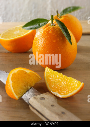 Whole and cut fresh oranges  with leaves in a kitchen - Stock Photo