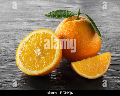 Whole and cut fresh oranges with leaves against a black background - Stock Photo