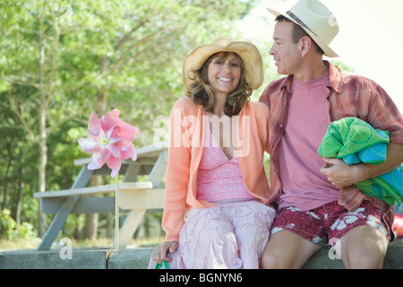 Mature couple sitting together and smiling - Stock Photo