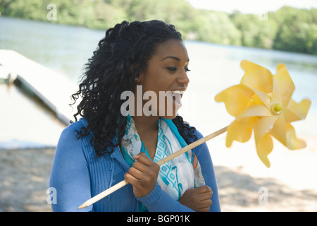 Close-up of a young woman holding a pinwheel - Stock Photo
