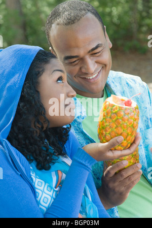 Close-up of a young woman and a mid adult man holding pineapples - Stock Photo
