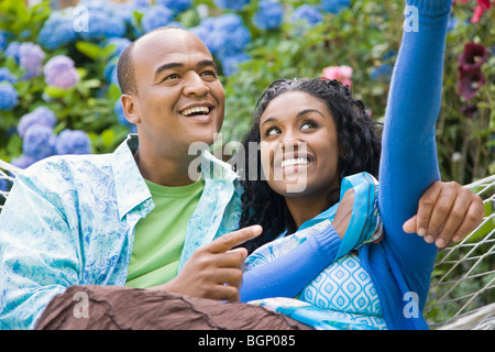 Close-up of a mid adult man and a young woman resting in a hammock - Stock Photo