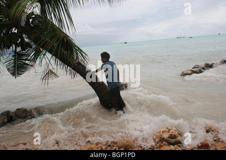 King tides flood property on Kiribati atoll - Stock Photo