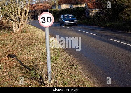 Thirty mile per hour speed limit road sign with car approaching - Stock Photo