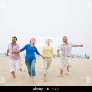 Two couples running on the beach with holding their hands - Stock Photo