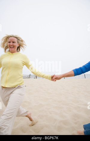 Mature woman running on the beach with holding her friend's hand - Stock Photo