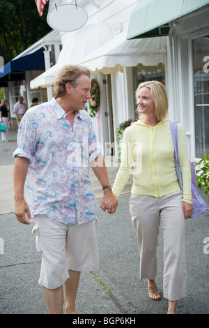 Mid adult woman and a mature man holding hands and walking - Stock Photo