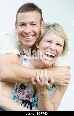 Portrait of a mature man embracing a mature woman from behind and smiling - Stock Photo