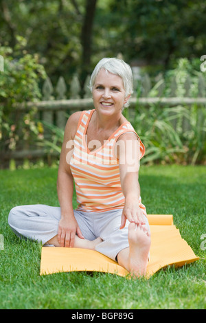 Mature woman exercising in a park - Stock Photo