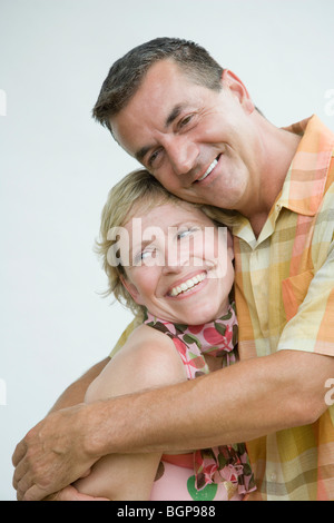 Close-up of a mature man hugging his wife and smiling - Stock Photo