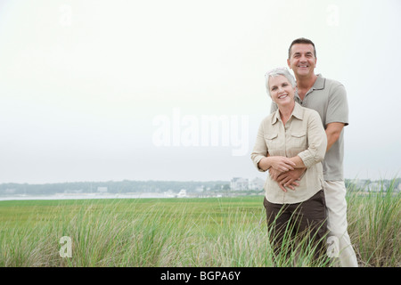 Portrait of a mature man embracing his wife from behind and smiling - Stock Photo