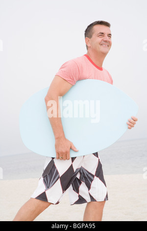 Side profile of a mature man carrying a body board on the beach - Stock Photo