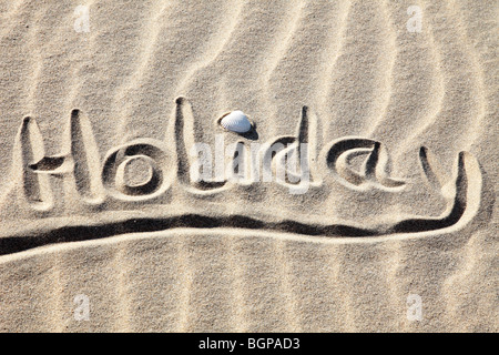 Holiday written in golden sand on a beach - Stock Photo