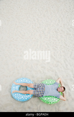 High angle view of a mature man lying on inflatable rings - Stock Photo