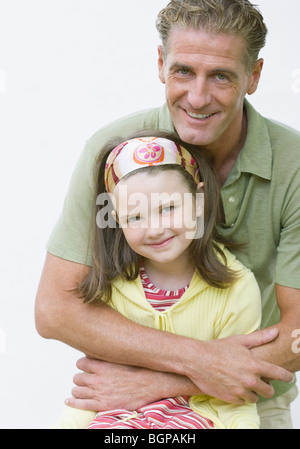 Portrait of a mature man hugging his daughter and smiling - Stock Photo