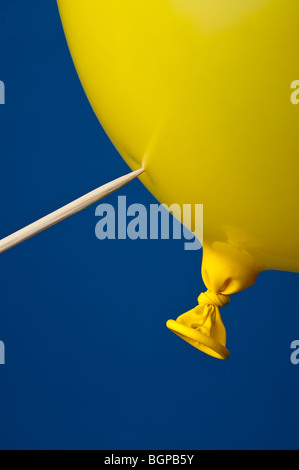 a pointed stick ready to pop a yellow balloon on blue - Stock Photo